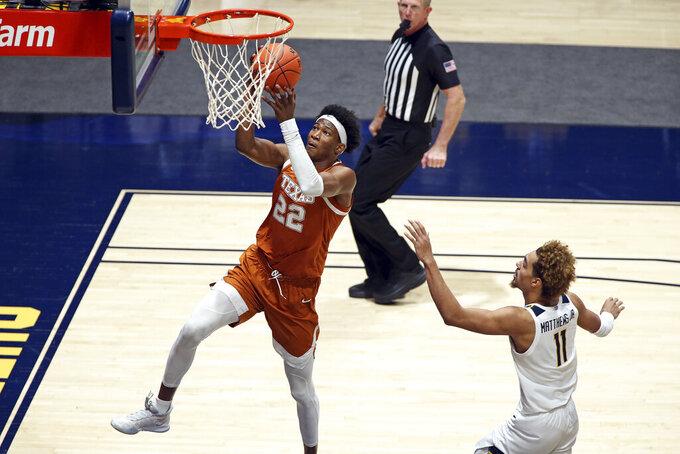 Texas forward Kai Jones (22) shoots while defended by West Virginia forward Emmitt Matthews Jr. (11) during the second half of an NCAA college basketball game Saturday, Jan. 9, 2021, in Morgantown, W.Va. (AP Photo/Kathleen Batten)