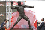 The covering is pulled off the bronze statue of former Cleveland Browns quarterback great Otto Graham by his grandson Ryan Vanname, left, and Cleveland Browns Executive Vice President JW Johnson, right, as Graham's wife, Beverly, watches during the Browns' unveiling ceremony, Saturday, Sept. 7, 2019, at FirstEnergy Stadium in Cleveland, Ohio. Graham's remarkable decade of dominance with the Browns has been immortalized. The team unveiled a bronze statue on Saturday, Sept. 7, 2019, outside FirstEnergy Stadium of the late Hall of Fame quarterback, who led Cleveland to 10 championship games in 10 seasons. (John Kuntz/cleveland.com via AP)
