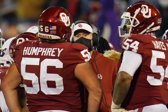 Oklahoma coach Lincoln Riley, center, talks with his players during the second half of an NCAA college football game against Baylor on Saturday, Dec. 5, 2020, in Norman, Okla. (AP Photo/Sue Ogrocki)