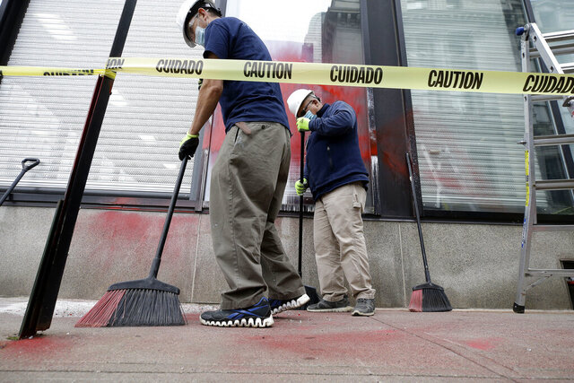 Workers sweep up broken glass from smashed windows, Tuesday, June 2, 2020, from the store front of a business in the downtown section of Providence, R.I. Authorities said the people who caused the damage in the early hours of Tuesday, June 2 were not protesting the death of George Floyd, the Minneapolis man who died after a police officer pressed his knee into his neck for several minutes even after he stopped moving and pleading for air. (AP Photo/Steven Senne)