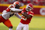 Kansas City Chiefs running back Clyde Edwards-Helaire, right, runs with the ball as Cleveland Browns linebacker Anthony Walker Jr. (4) defends during the second half of an NFL football game Sunday, Sept. 12, 2021, in Kansas City, Mo. (AP Photo/Charlie Riedel)