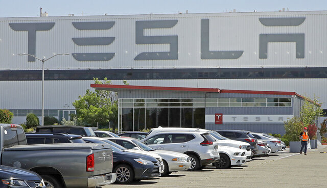 FILE - In this Monday, May 11, 2020 file photo, a man wearing a mask walks through the Tesla plant parking lot in Fremont, Calif. On Wednesday, July 22, 2020, the electric car maker announced it has picked the Austin, Texas, area as the site for its largest auto assembly plant employing at least 5,000 workers. (AP Photo/Ben Margot)