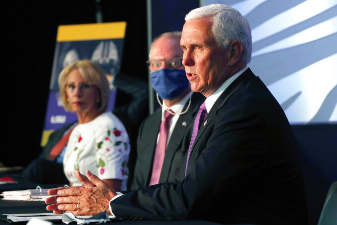 Education Secretary Betsy DeVos listens with Louisiana Gov. John Bel Edwards as Vice President Mike Pence speaks at a roundtable discussion in Tiger Stadium on the LSU campus in Baton Rouge, La., Tuesday, July 14, 2020. (AP Photo/Gerald Herbert)