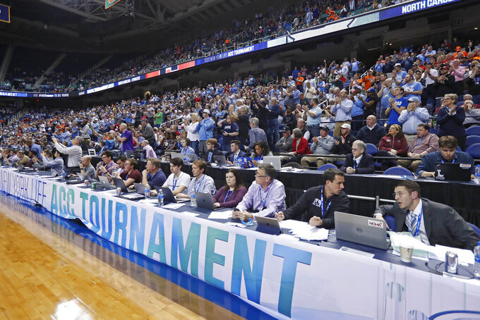 Fans and media watch during an NCAA college basketball game between North Carolina and Syracuse at the Atlantic Coast Conference tournament in Greensboro, N.C., Wednesday, March 11, 2020. The ACC announced it will close the remainder of its men's basketball tournament to spectators, beginning with Thursday's quarterfinals, amid the emerging threat of the spread of the coronavirus. (AP Photo/Gerry Broome)