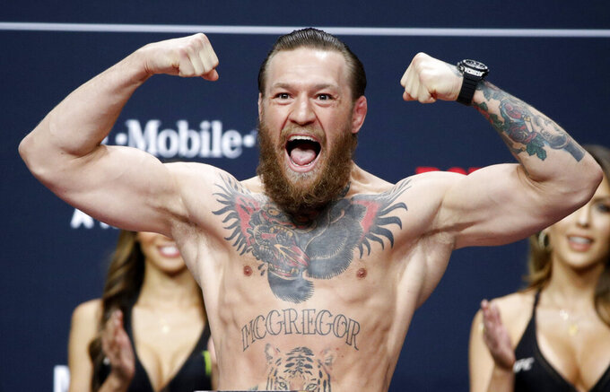 FILE - Conor McGregor poses during a ceremonial weigh-in for the UFC 246 mixed martial arts bout in Las Vegas, in this Friday, Jan. 17, 2020, file photo. The UFC intends to welcome a capacity crowd at Las Vegas' T-Mobile Arena on July 10, 2021, when Dustin Poirier and Conor McGregor fight for the third time. UFC President Dana White announced his plan Wednesday, April 14, 2021, for the promotion's first sellout show in its hometown since the start of the coronavirus pandemic.(AP Photo/John Locher, File)