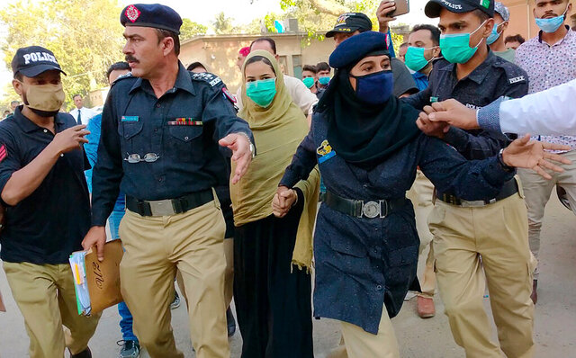 Police officers escort Arzoo Raja, background center, after her appearance in Sindh High Court, in Karachi, Pakistan, on Nov. 3, 2020. Raja was 13 when she disappeared from her home in central Karachi. The Christian girl's parents reported her missing and pleaded with police to find her. Two days later, officers reported back that she had been converted to Islam and was married to their 40-year-old Muslim neighbor. (AP Photo/Fareed Khan)