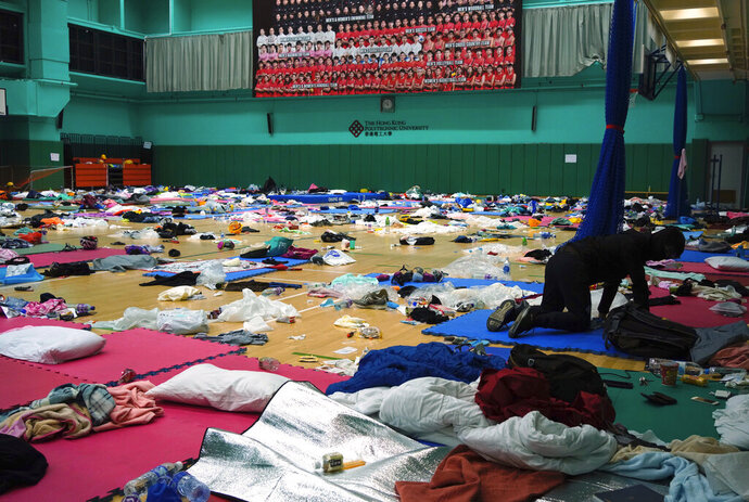 A protester sits in a gymnasium at Hong Kong Polytechnic University in Hong Kong, Tuesday, Nov. 19, 2019. A small band of anti-government protesters, their numbers diminished by various surrenders and failed escape attempts, have remained holed up at a Hong Kong university as they braced for the endgame in a police siege of the campus that has entered its third day. (AP Photo/Vincent Yu)