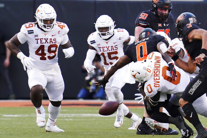 Oklahoma State running back LD Brown (0) fumbles as he is tackled by Texas linebacker DeMarvion Overshown (0) in the second half of an NCAA college football game in Stillwater, Okla., Saturday, Oct. 31, 2020. (AP Photo/Sue Ogrocki)