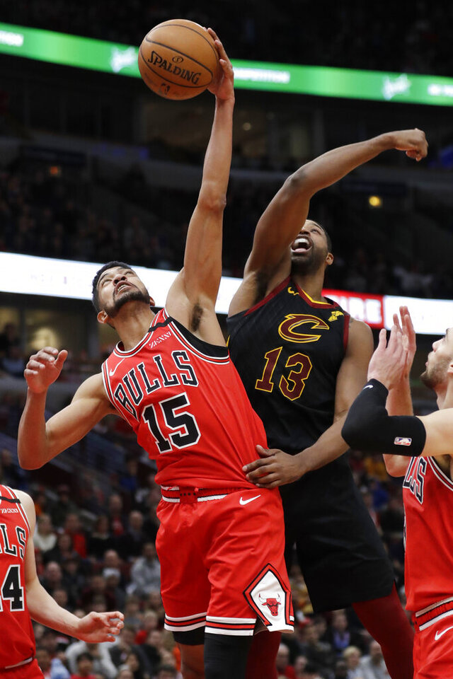 Chicago Bulls forward Chandler Hutchison, left, pulls down a rebound next to Cleveland Cavaliers' Tristan Thompson during the second half of an NBA basketball game in Chicago, Saturday, Jan. 18, 2020. The Bulls won 118-116. (AP Photo/Nam Y. Huh)