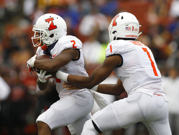 Illinois quarterback AJ Bush Jr., right, hands off to running back Reggie Corbin, who ran for a touchdown on the play during the first half of an NCAA college football game against Rutgers, Saturday, Oct. 6, 2018, in Piscataway, N.J. (AP Photo/David Boe)