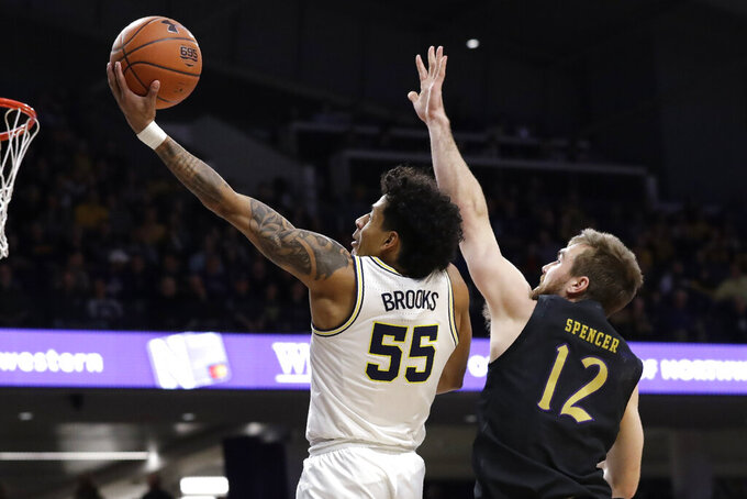 Michigan guard Eli Brooks, left, drives to the basket past Northwestern guard Pat Spencer during the first half of an NCAA college basketball game in Evanston, Ill., Wednesday, Feb. 12, 2020. (AP Photo/Nam Y. Huh)