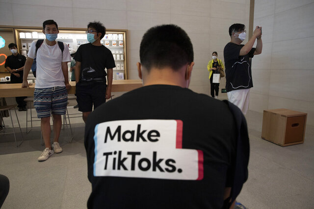 FILE - In this July 17, 2020, file photo, a man wearing a shirt promoting TikTok is seen at an Apple store in Beijing, China. TikTok's parent company ByteDance has chosen Oracle over Microsoft as a new American technology partner to help keep the popular video-sharing app operating in the U.S., according to a person familiar with the deal.(AP Photo/Ng Han Guan, File)