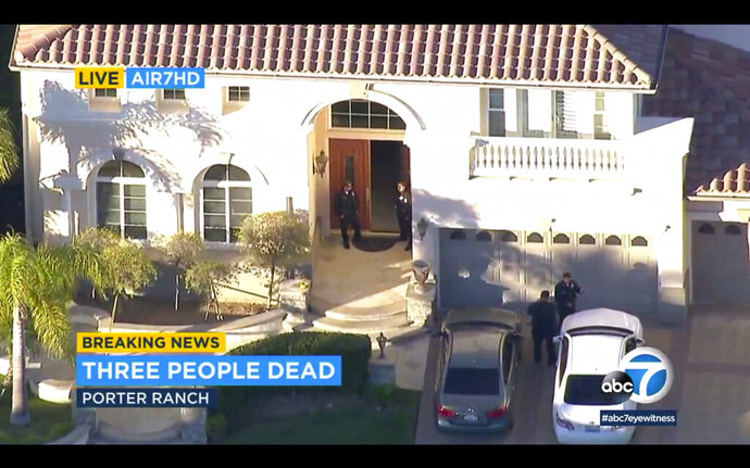 In this still image taken from Live Air7HD aerial video courtesy of KABC-TV, Los Angeles police officers secure a residence in Porter Ranch, northwest of Los Angeles, Monday, Feb. 18, 2019. Several people were found dead following reports of gunfire at this home in the upscale gated community.  (KABC-TV via AP)