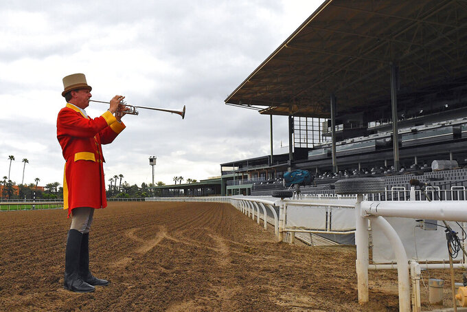 "Bugler Jay Cohen plays ""First Call"" as he calls the riders to post for the first race at Santa Anita Park to empty stands Saturday, March 14, 2020, in Arcadia, Calif. While most of the sports world is idled by the coronavirus pandemic, horse racing runs on. (AP Photo/Mark J. Terrill)"