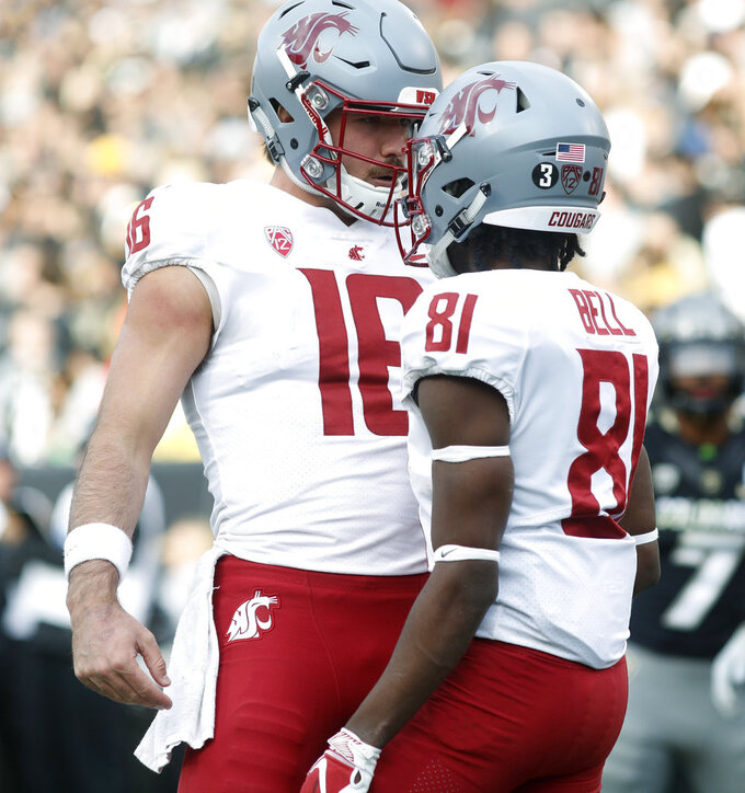 Washington State quarterback Gardner Minshew, left, congratulates wide receiver Renard Bell after his touchdown catch against Colorado in the second half of an NCAA college football game Saturday, Nov. 10, 2018, in Boulder, Colo. Washington State won 31-7. (AP Photo/David Zalubowski)