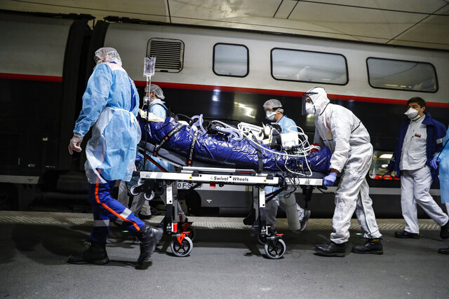 FILE - In this April 1, 2020 file photo, medical staff transfer a patient infected with the coronavirus to a train at the Gare d'Austerlitz train station in Paris. On high-speed trains fitted out like hospitals and military planes, France has moved hundreds of intensive care patients around the country in an exceptional effort to relieve congested hospitals and stay ahead of the fast-moving virus. The new coronavirus causes mild or moderate symptoms for most people, but for some, especially older adults and people with existing health problems, it can cause more severe illness or death. (Thomas Samson, Pool via AP, File)