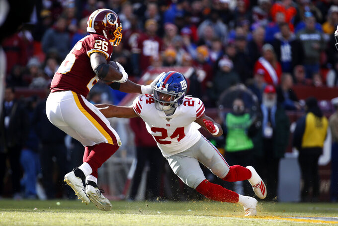 Washington Redskins running back Adrian Peterson (26) runs with the ball as New York Giants cornerback Julian Love (24) moves in for the tackle during the first half of an NFL football game, Sunday, Dec. 22, 2019, in Landover, Md. (AP Photo/Alex Brandon)