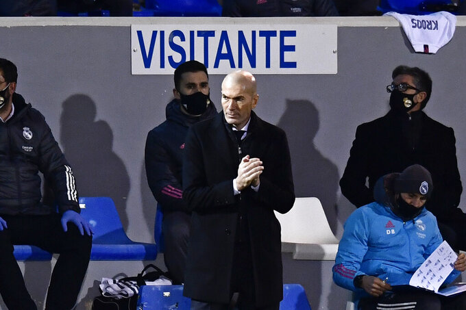 FILE- In this Wednesday, Jan. 20, 2021 file photo, Real Madrid's head coach Zinedine Zidane applauds during a Spanish Copa del Rey round of 32 soccer match between Alcoyano and Real Madrid at the El Collao stadium in Alcoy, Spain. Zidane has tested positive for the coronavirus. The Spanish club's announcement comes two days after Zidane coached the team in a 2-1 loss at third-tier Alcoyano in the Copa del Rey. The club has not provided other information on his health status. Madrid plays at Alavés in the Spanish league on Saturday. (AP Photo/Jose Breton, File)