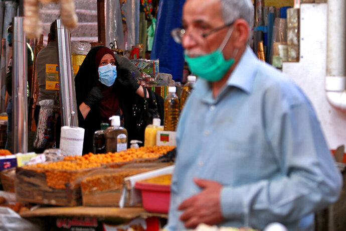 People shop in preparation for the Muslim fasting month of Ramadan, in Baghdad, Iraq, Tuesday, April 21, 2020. Ramadan begins with the new moon later this week, Muslims all around the world are trying to work out how to maintain the many cherished rituals of Islam's holiest month. (AP Photo/Hadi Mizban)