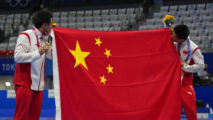 Cao Yuan of China, left, gold medal and Yang Jian of China, silver medal kiss their flag after men's diving 10m platform final at the Tokyo Aquatics Centre at the 2020 Summer Olympics, Saturday, Aug. 7, 2021, in Tokyo, Japan. (AP Photo/Dmitri Lovetsky)