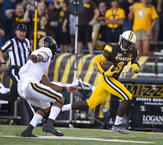 Wyoming defender Alijah Halliburton, right, runs a fumble recovery for a touchdown past Missouri quarterback Kelly Bryant during the second quarter of an NCAA college football game Saturday, Aug. 31, 2019, in Laramie, Wy. (AP Photo/Michael Smith)