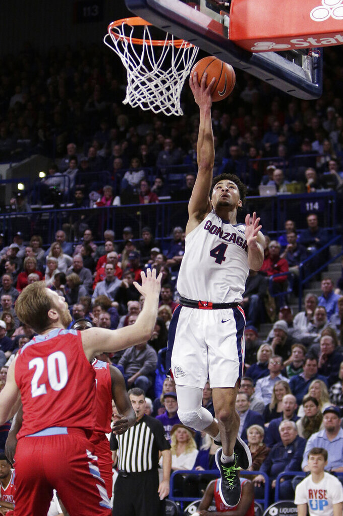 Gonzaga guard Ryan Woolridge (4) shoots in front of Loyola Marymount guard Erik Johansson (20) during the first half of an NCAA college basketball game in Spokane, Wash., Thursday, Feb. 6, 2020. (AP Photo/Young Kwak)