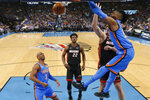 Oklahoma City Thunder center Nerlens Noel, right, dunks in front of teammate Chris Paul (3) and Miami Heat forwards Jimmy Butler (22) and Meyers Leonard, behind Noel, during the first half of an NBA basketball game Friday, Jan. 17, 2020, in Oklahoma City. (AP Photo/Sue Ogrocki)
