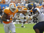 Tennessee's Tim Jordan (9) runs as West Virginia's Kenny Bigelow Jr. (40) defends in the first half of an NCAA college football game in Charlotte, N.C., Saturday, Sept. 1, 2018. (AP Photo/Chuck Burton)