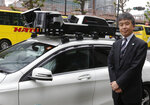 In this May 31, 2018, photo, Mitsubishi Electric Corp. Senior General Manager Yasuhide Shibata, who oversees the mapping project, stands next to a car equipped with some of the devices for making the 3D digital maps at the company's headquarters in Tokyo. Technology companies are racing to develop ultra-precise three-dimensional digital maps that can guide self-driving cars to within inches of where they are supposed to be _ a hurdle the industry needs to clear if it hopes to deliver on its promise of widespread use of driverless vehicles. (AP Photo/Yuri Kageyama)