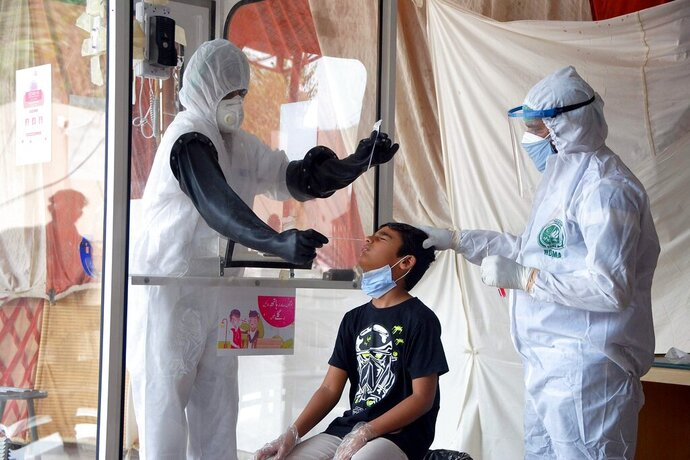 FILE - In this Friday, June 26, 2020 file photo, health workers take a nasal swab sample during a testing and screening operation for the new coronavirus, in Hyderabad, Pakistan. (AP Photo/Pervez Masih, File)
