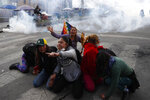 Supporter of former President Evo Morales protect themselves from tear gas launched by the police, in La Paz, Bolivia, Friday, Nov. 15, 2019. Bolivia's new interim president Jeanine Anez faces the challenge of stabilizing the nation and organizing national elections within three months at a time of political disputes that pushed Morales to fly off to self-exile in Mexico after 14 years in power. (AP Photo/Natacha Pisarenko)