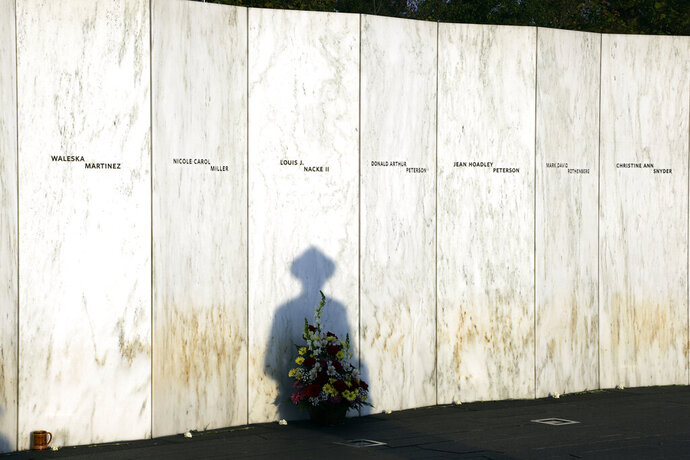 FILE - In this Sept. 11, 2019, file photo a Pennsylvania State Trooper pauses in front of the Wall of Names at the Flight 93 National Memorial in Shanksville, Pa. before a Service of Remembrance as the nation marks the 18th anniversary of the Sept. 11, 2001 attacks. The Wall of Names honor the 40 people killed in the crash of Flight 93. Both President Donald Trump and Democratic challenger Joe Biden will commemorate the 19th anniversary of the Sept. 11 attacks in rural Pennsylvania where one of the hijacked planes crashed in a field. (AP Photo/Gene J. Puskar, File)