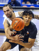 Georgia Tech's Jose Alvarado, rear, knocks the ball away from Miami's Isaiah Wong during an NCAA college basketball game in the quarterfinal round of the Atlantic Coast Conference tournament in Greensboro, N.C., Thursday, March 11, 2021. (Woody Marshall/News & Record via AP)