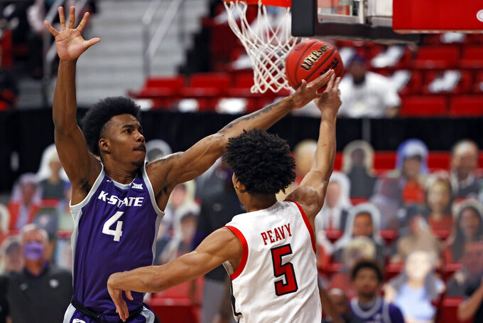 Texas Tech's Micah Peavy (5) passes the ball around Kansas State's Seryee Lewis (4) during the first half of an NCAA college basketball game Tuesday, Jan. 5, 2021, in Lubbock, Texas. (AP Photo/Brad Tollefson)