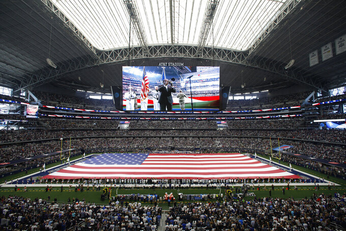 A field sized U.S. flag is unfurled during the playing of the national anthem inside AT&T Stadium before the first half of a NFL football game between the New York Giants and Dallas Cowboys in Arlington, Texas, Sunday, Sept. 8, 2019. (AP Photo/Roger Steinman)