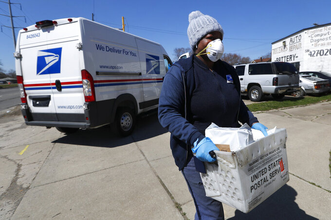 A United States Postal worker makes a delivery with gloves and a mask in Warren, Mich., Thursday, April 2, 2020. The U.S. Postal Service is keeping post offices open but ensuring customers stay at least 6 feet (2 meters) apart. The agency said it is following guidance from public health experts, although there is no indication that the new coronavirus COVID-19 is being spread through the mail. (AP Photo/Paul Sancya)