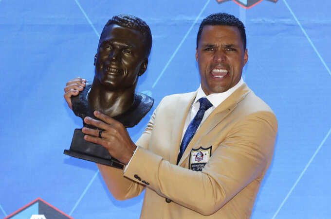 Former NFL player Tony Gonzalez holds up his Pro Football Hall of Fame bust during inductions at the hall Saturday, Aug. 3, 2019, in Canton, Ohio. (AP Photo/Ron Schwane)
