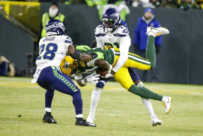 Green Bay Packers' Geronimo Allison is stopped by Seattle Seahawks' Ugo Amadi (28) and Tre Flowers (21) during the first half of an NFL divisional playoff football game Sunday, Jan. 12, 2020, in Green Bay, Wis. (AP Photo/Mike Roemer)