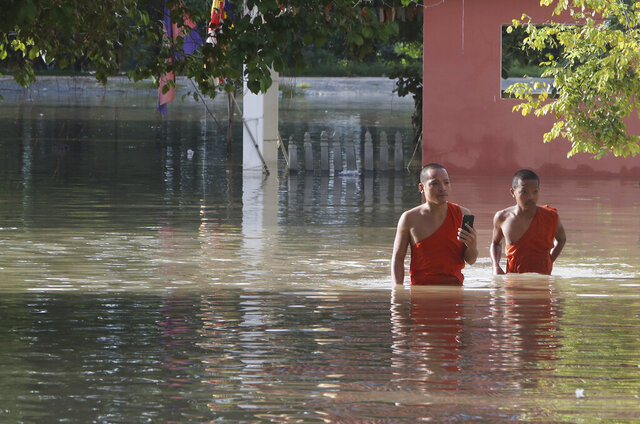 Buddhist monks walk through a flooded pagoda following recent rains on the outskirts of Phnom Penh, Cambodia, Wednesday, Oct. 14, 2020. A Cambodian disaster official said Wednesday that more than 10,000 people have been evacuated to safety places after a tropical storm hit the country, causing the flash flood. (AP Photo/Heng Sinith)