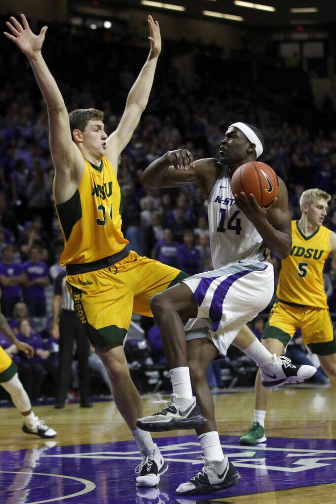 Kansas State forward Makol Mawien (14) charges into North Dakota State forward Rocky Kreuser, left, during the second half of an NCAA college basketball game in Manhattan, Kan., Tuesday, Nov. 5, 2019. Kansas State defeated North Dakota State 67-54. (AP Photo/Orlin Wagner)