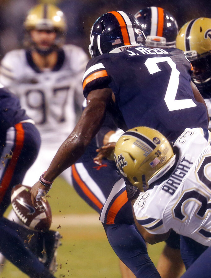 Virginia wide receiver Joe Reed (2) loses the ball as Pittsburgh linebacker Cam Bright (38) tackles him during the first half of an NCAA college football game in Charlottesville, Va., Friday, Nov. 2, 2018. (AP Photo/Steve Helber)