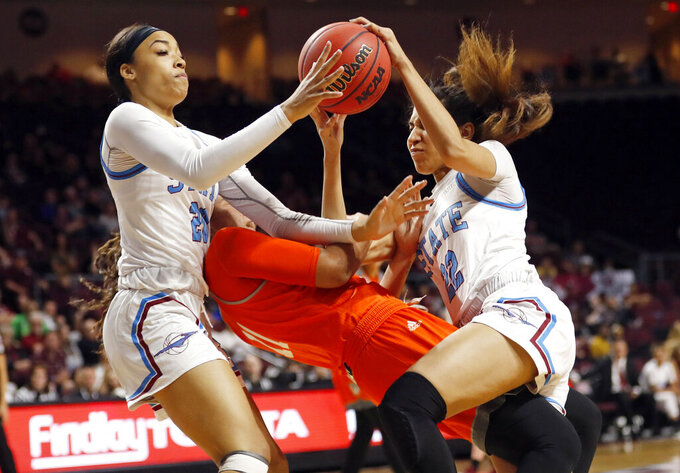 New Mexico State guard Dominique Mills (20) and teammate Kalei Atkinson (22) go after a loose ball over Texas-Rio Grande Valley guard Quynne Huggins (11) during a NCAA college basketball Western Athletic Conference Women's Tournament championship game Saturday, March 16, 2019, in Las Vegas. (AP Photo/Steve Marcus)