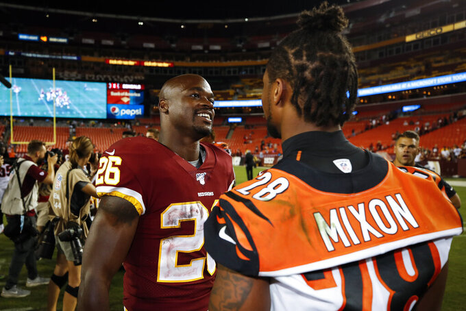 Washington Redskins running back Adrian Peterson (26) and Cincinnati Bengals running back Joe Mixon (28) talk after an NFL preseason football game Thursday, Aug. 15, 2019, in Landover, Md. The Bengals won 23-13. (AP Photo/Alex Brandon)
