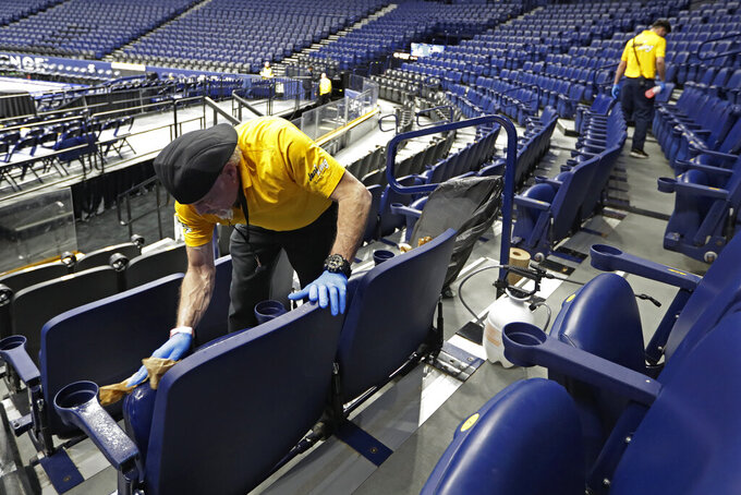 Luis Rivera, left, sanitizes seats in Bridgestone Arena after the remaining NCAA college basketball games in the Southeastern Conference tournament were canceled Thursday, March 12, 2020, in Nashville, Tenn. (AP Photo/Mark Humphrey)