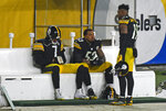 Pittsburgh Steelers quarterback Ben Roethlisberger (7) and center Maurkice Pouncey (53) sit on the bench as they talk with wide receiver JuJu Smith-Schuster (19) following a 48-37 loss to the Cleveland Browns in an NFL wild-card playoff football game in Pittsburgh, late Sunday, Jan. 10, 2021. (AP Photo/Don Wright)