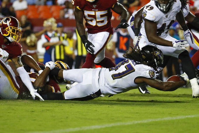 Washington Redskins cornerback Ashton Lampkin, left, and linebacker Andrew Ankrah combine but cannot stop a first down by Baltimore Ravens running back De'Lance Turner (47) during the second half of an NFL preseason football game Thursday, Aug. 29, 2019, in Landover, Md. (AP Photo/Alex Brandon)