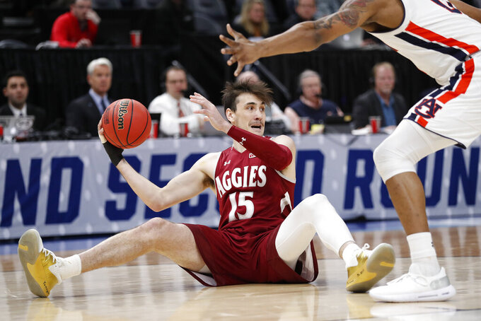 New Mexico State forward Ivan Aurrecoechea (15) looks to pass against Auburn's forward Horace Spencer, right, in the first half during a first round men's college basketball game in the NCAA Tournament, Thursday, March 21, 2019, in Salt Lake City. (AP Photo/Jeff Swinger)