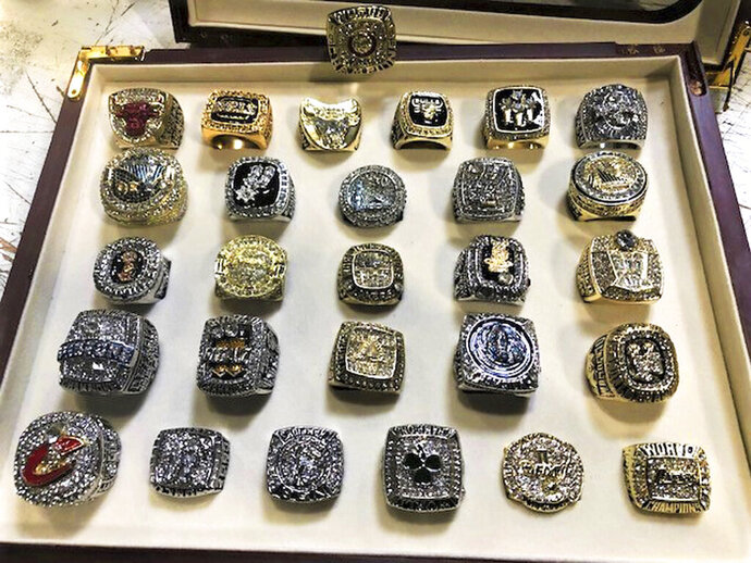 This undated photo provided by U.S. Customs and Border Protection shows a collection of counterfeit NBA championship rings that have been seized by federal authorities at Los Angeles International Airport. CBP said Wednesday, Sept. 11, 2019 that the rings were in a wooden box shipped from China with a final destination in Arizona. Investigators suspect the intent was to sell the phony rings as a collection. (U.S. Customs and Border Protection via AP)