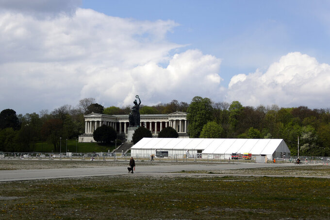 A woman and her dog walk by the 'Oktoberfest' beer festival area 'Theresienwiese' in front of the Bavaria statue and a corona test centre in Munich, Germany, Monday, May 3, 2021. The world's largest beer festival 'Oktoberfest' was cancelled last year due to the coronavirus outbreak. (AP Photo/Matthias Schrader)