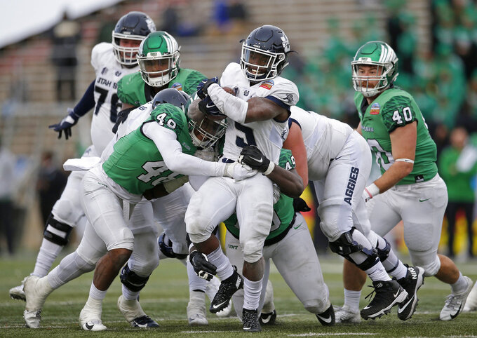 Utah State running back Darwin Thompson (5) tries to break away from North Texas defenders during the second half of the New Mexico Bowl NCAA college football game in Albuquerque, N.M., Saturday, Dec. 15, 2018. Utah State won 52-13. (AP Photo/Andres Leighton)